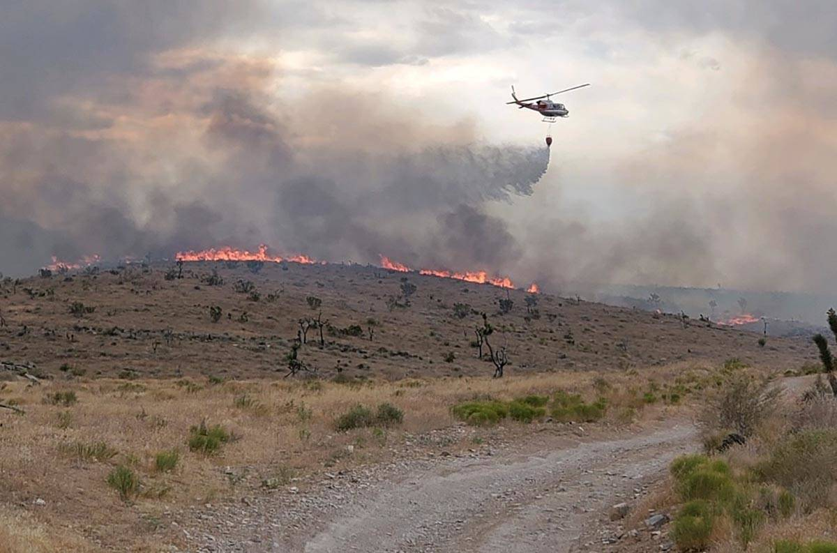 A helicopter is used to battle flames at the Cottonwood Fire north of Goodsprings and southwest ...