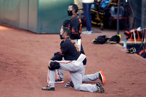 San Francisco Giants' manager Gabe Kapler kneels during the national anthem prior to an exhibit ...