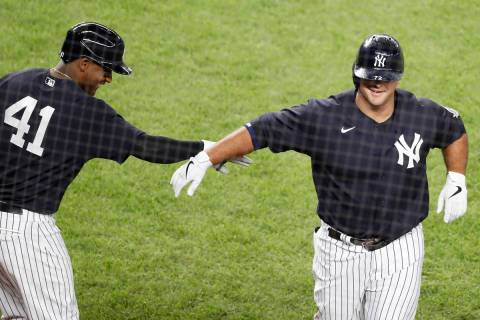 New York Yankees Miguel Andujar (41) congratulates Mike Ford after Ford hit a ninth-inning, sol ...