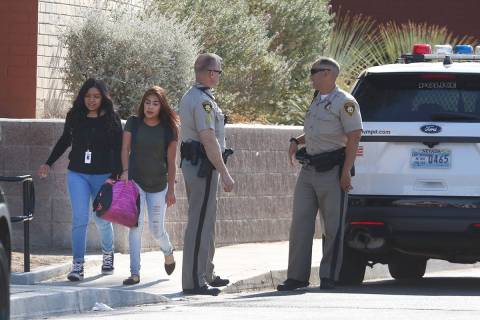 Students at Clark High School walk past Las Vegas police officers at their school Monday, Oct. ...