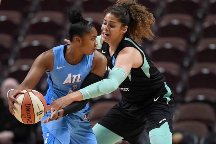Atlanta Dream's Alex Bentley is pressured by New York Liberty's Amanda Zahui B. Of Sweden durin ...