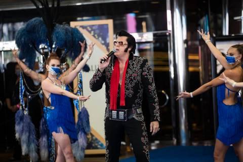 Brendan Paul, impersonating Elvis Presley, addresses the crowd alongside dancers at the reopeni ...