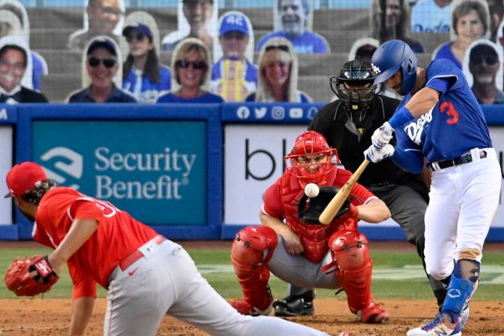 Los Angeles Dodgers' Chris Taylor, right, hits a three-run home run as Los Angeles Angels pitch ...