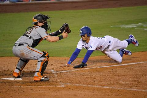 Los Angeles Dodgers' Mookie Betts, right, scores on a fielder's choice hit by Justin Turner as ...