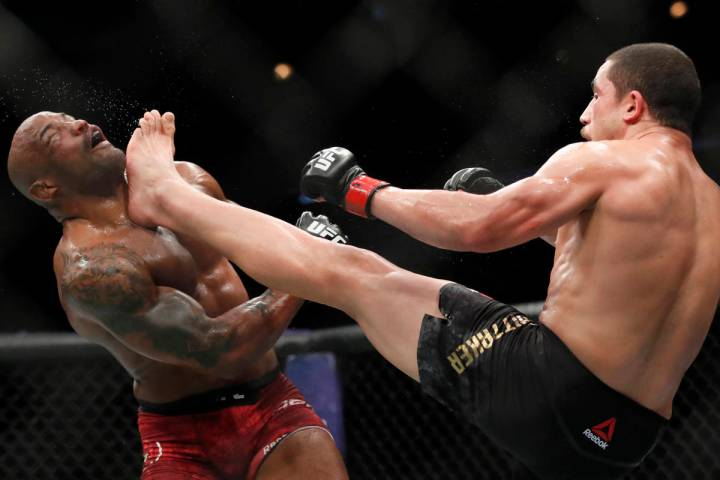 Robert Whittaker, right, kicks Yoel Romero in the face during their middleweight title mixed ma ...
