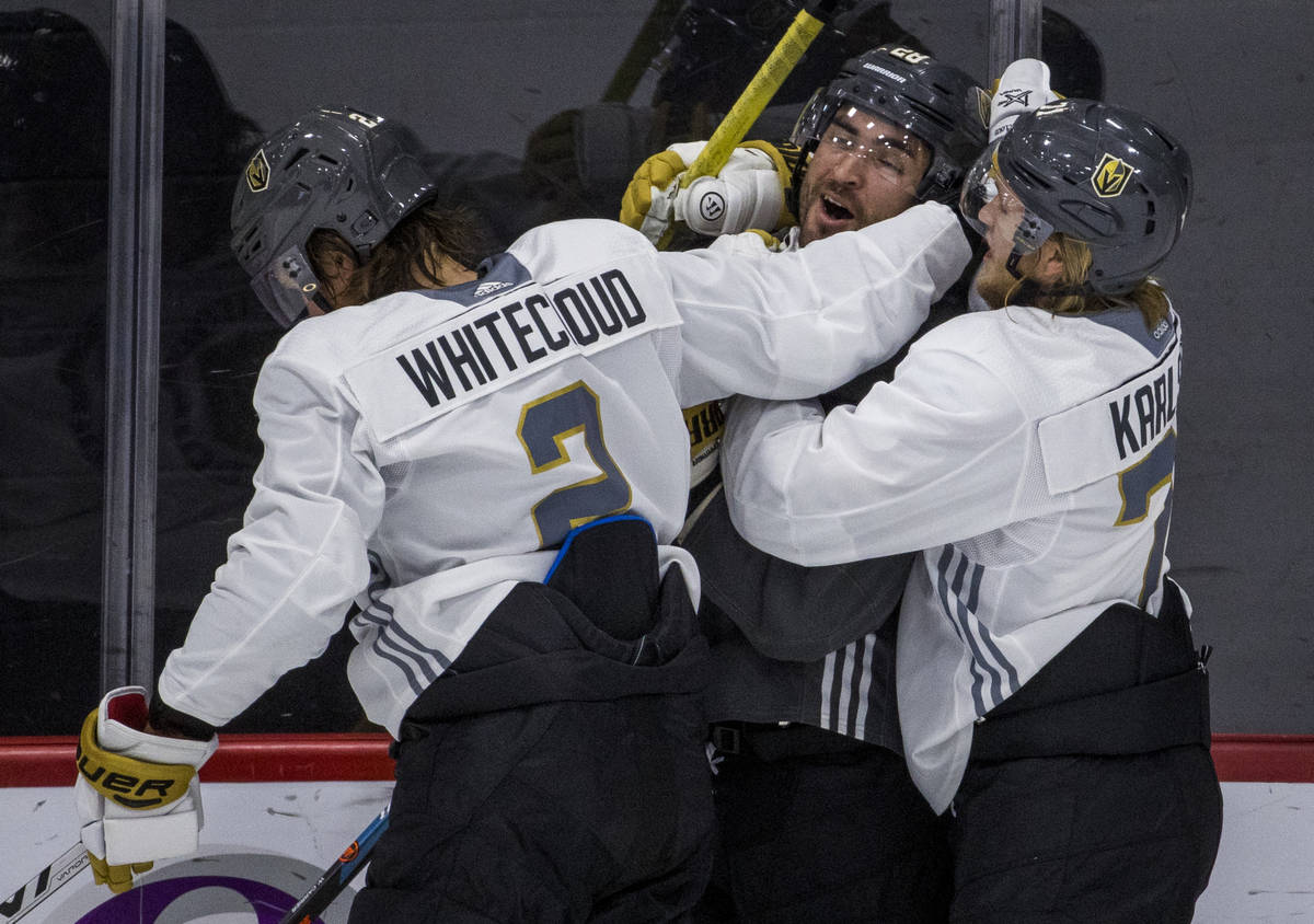 Vegas Golden Knights left wing William Carrier (28, center) is wrapped up by defenseman Zach Wh ...