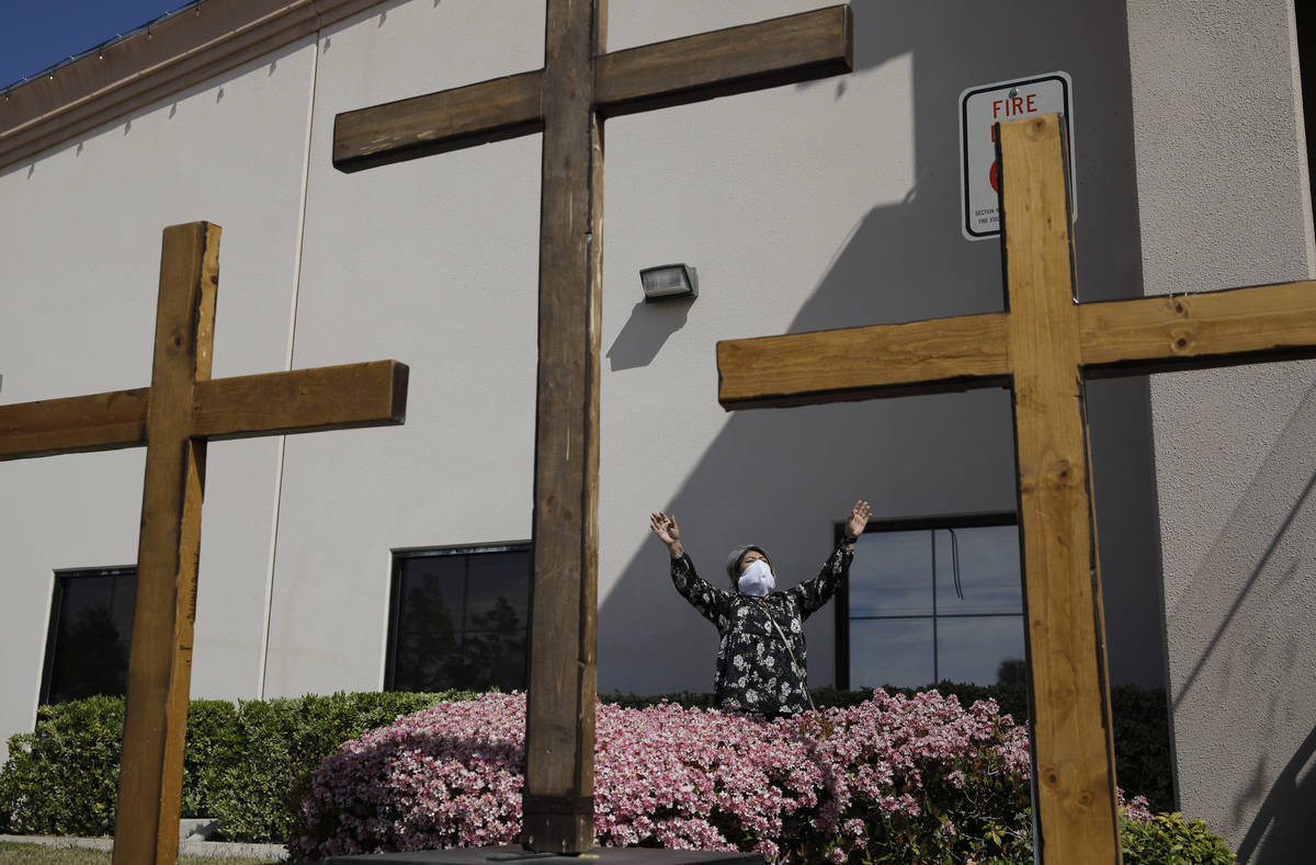 Norma Urrabazo prays while wearing a facemask before speaking at an Easter drive-in service at ...