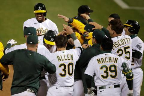 Oakland Athletics players celebrate after Matt Olson, center left, hit a grand slam home run ag ...