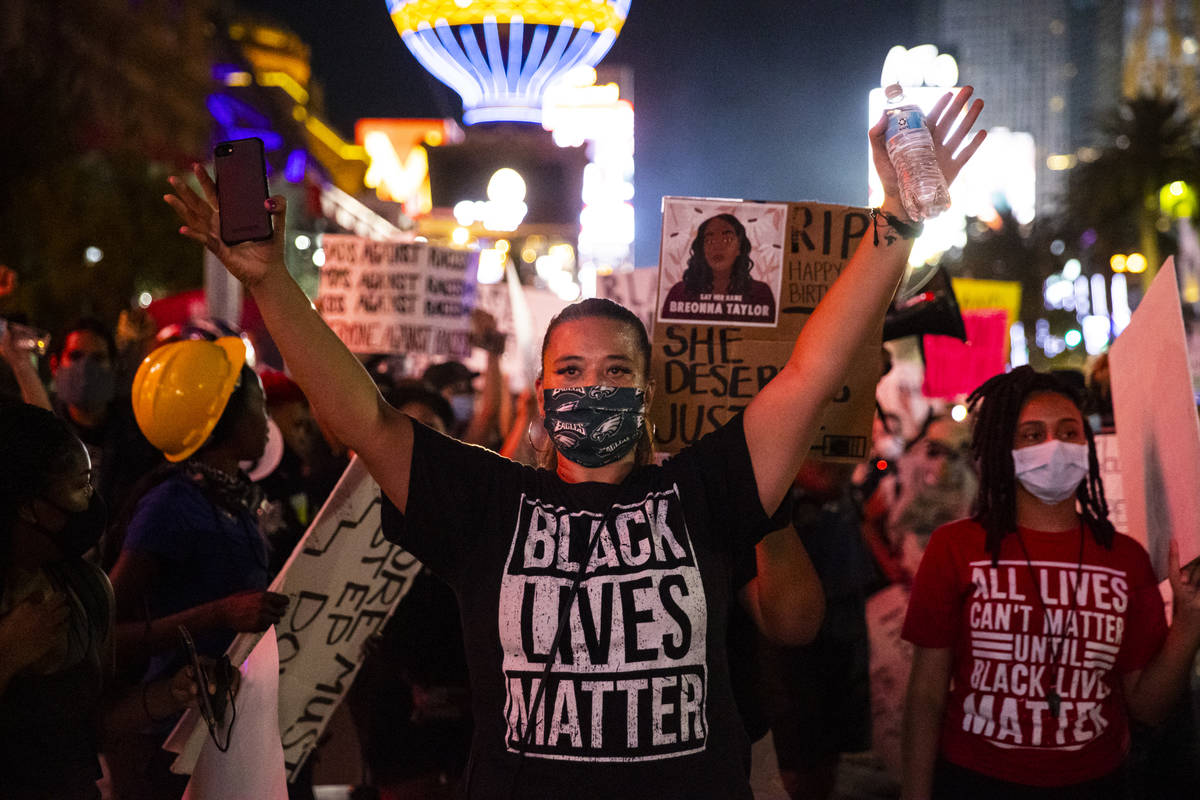 Leinati Hackley raises her hands during a Black Lives Matter march on the Las Vegas Strip on Sa ...