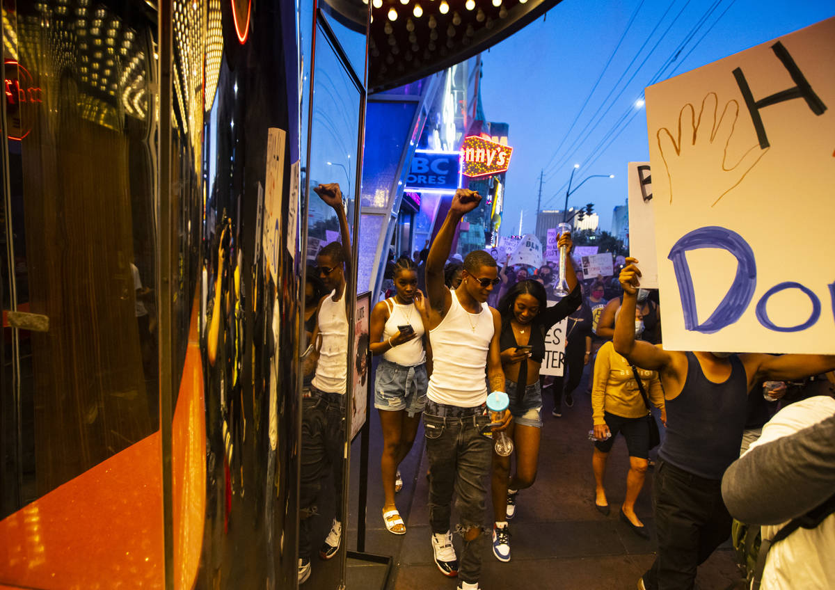 Tourists raise their fists in solidarity as people march during a Black Lives Matter rally on t ...
