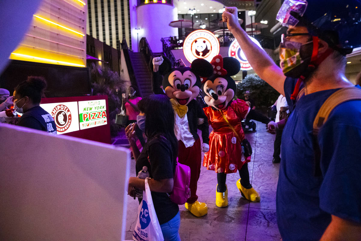 Street performers look as Black Lives Matter protesters walk on the Las Vegas Strip on Saturday ...