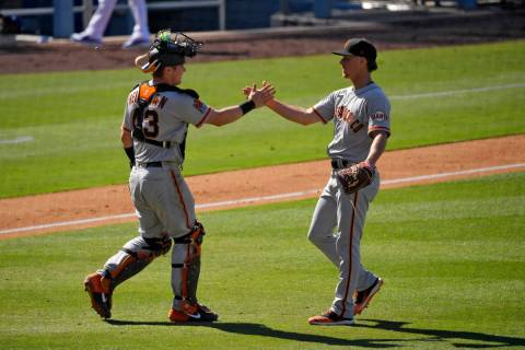 San Francisco Giants catcher Tyler Heineman, left, and relief pitcher Trevor Gott congratulate ...