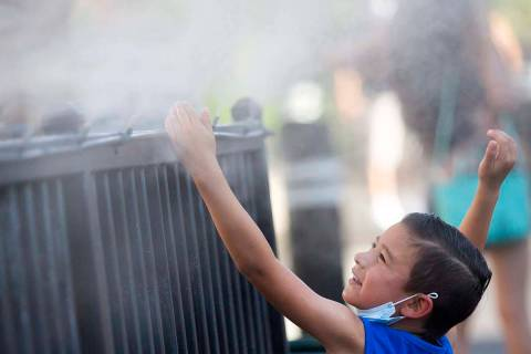 Brody Lester, 5, of California, cools off with the mist outside Hexx Bar and Grill's patio on t ...