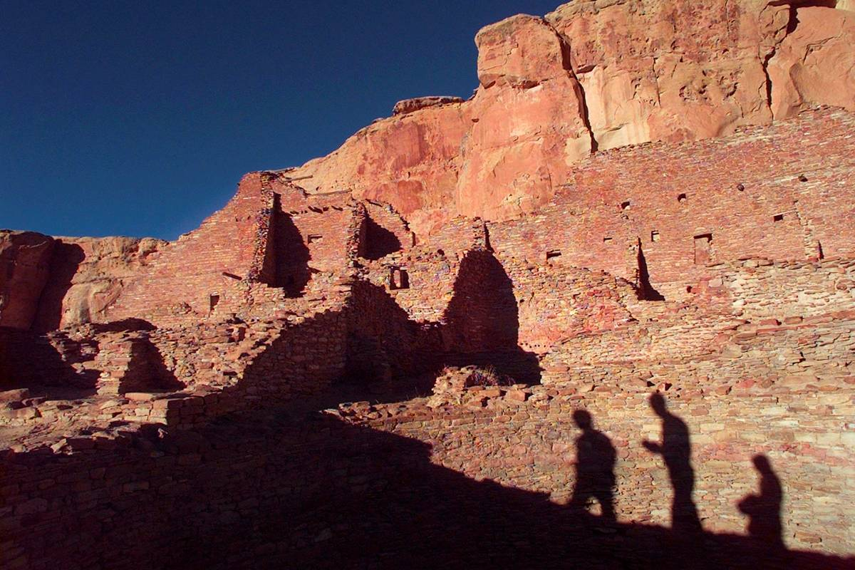 Tourists cast their shadows on the ancient Anasazi ruins of Chaco Culture National Historical P ...