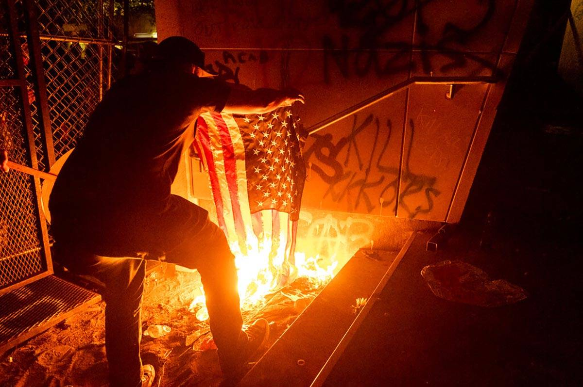 A Black Lives Matter protester burns an American flag outside the Mark O. Hatfield United State ...