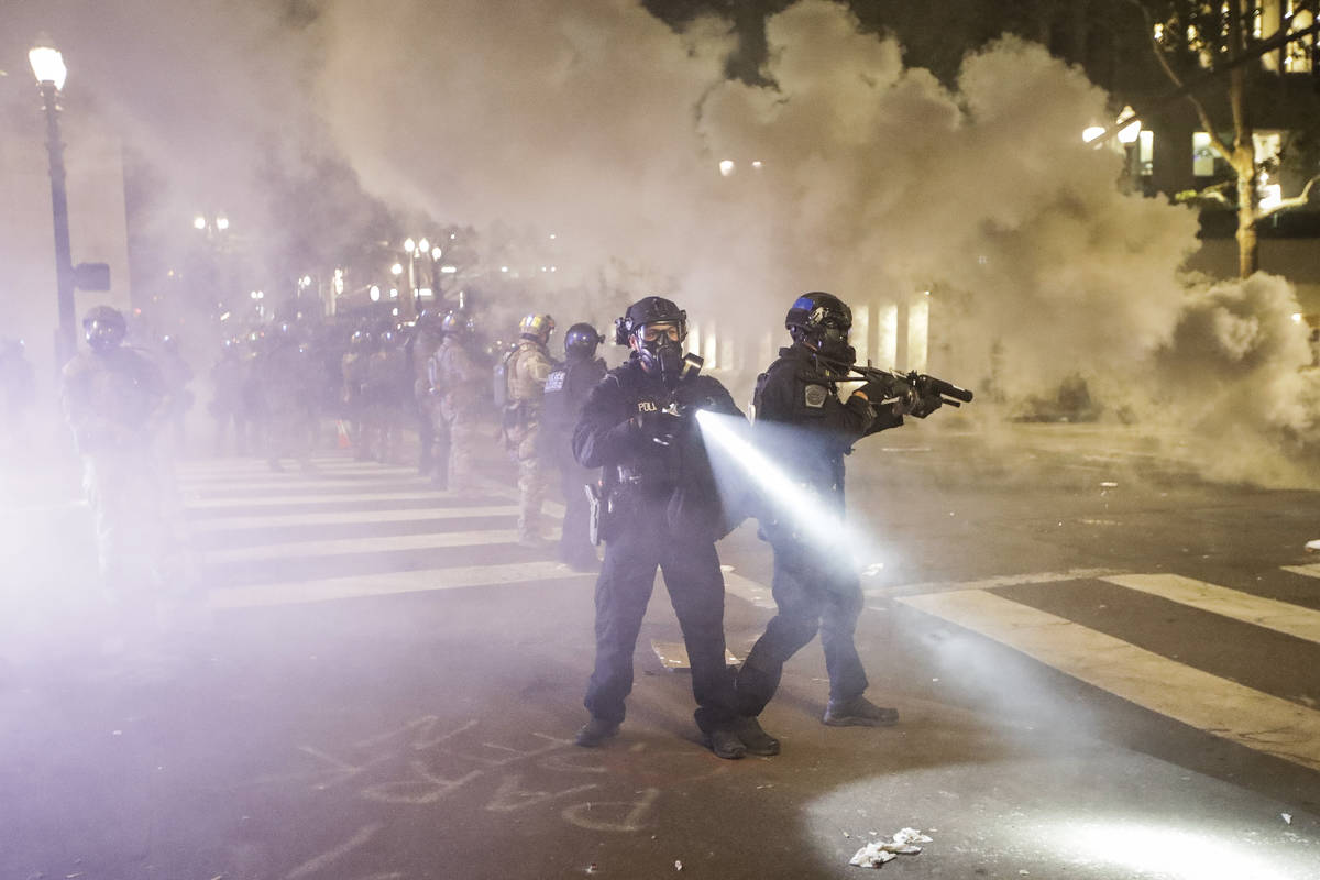 Federal officers deploy tear gas and crowd control munitions at demonstrators during a Black Li ...