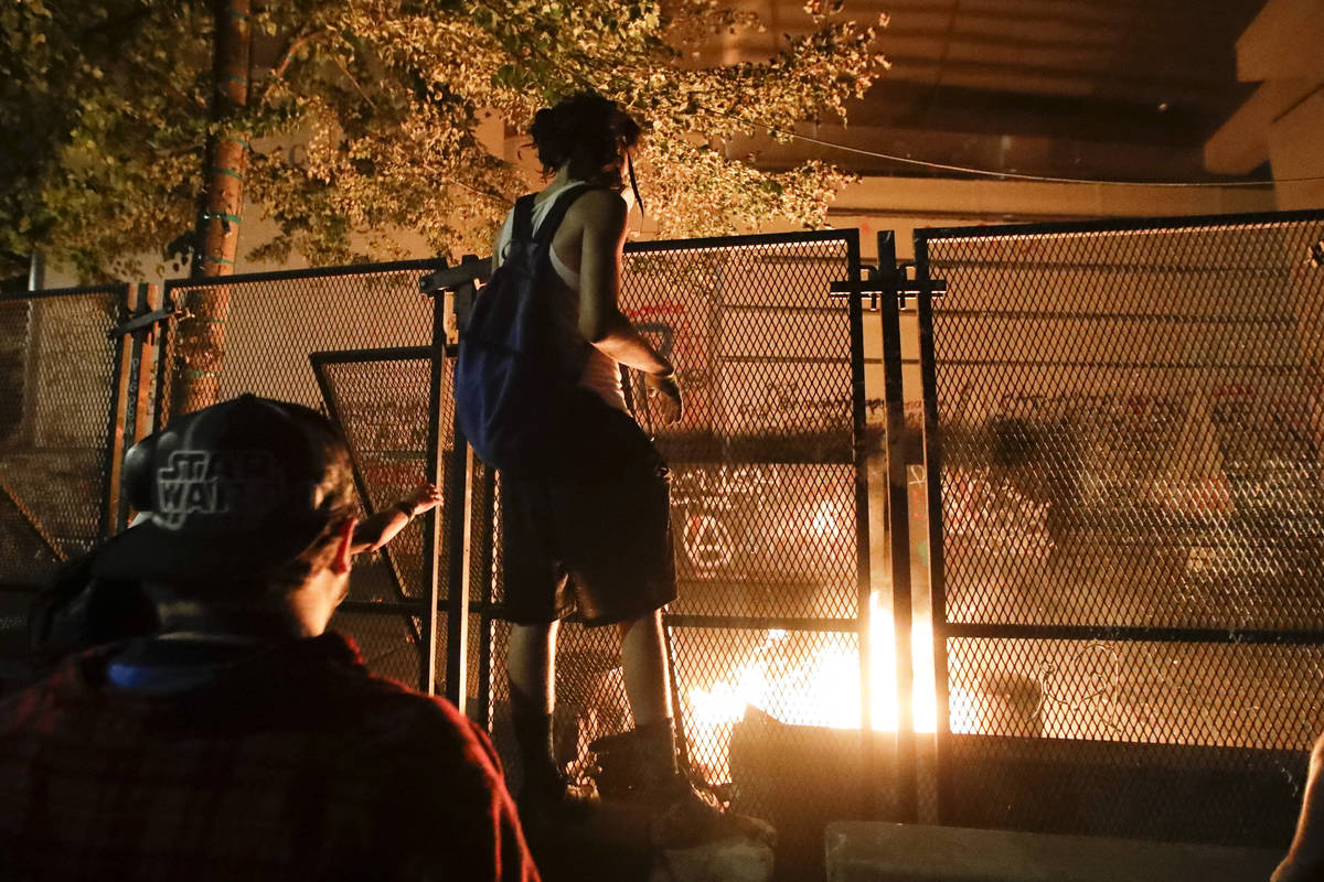 Demonstrators light a fire during a Black Lives Matter protest at the Mark O. Hatfield United S ...