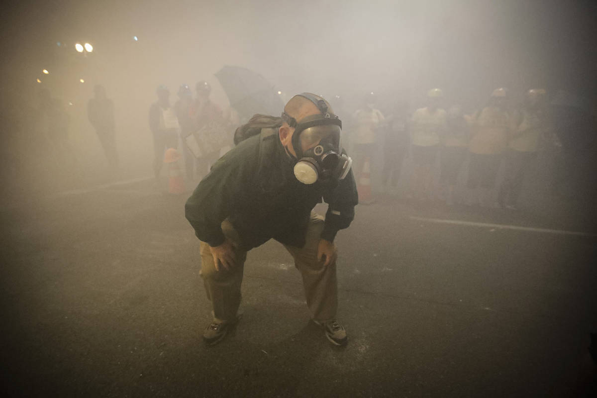 A demonstrator wears a gas mask as federal officers deploy tear gas during a Black Lives Matter ...