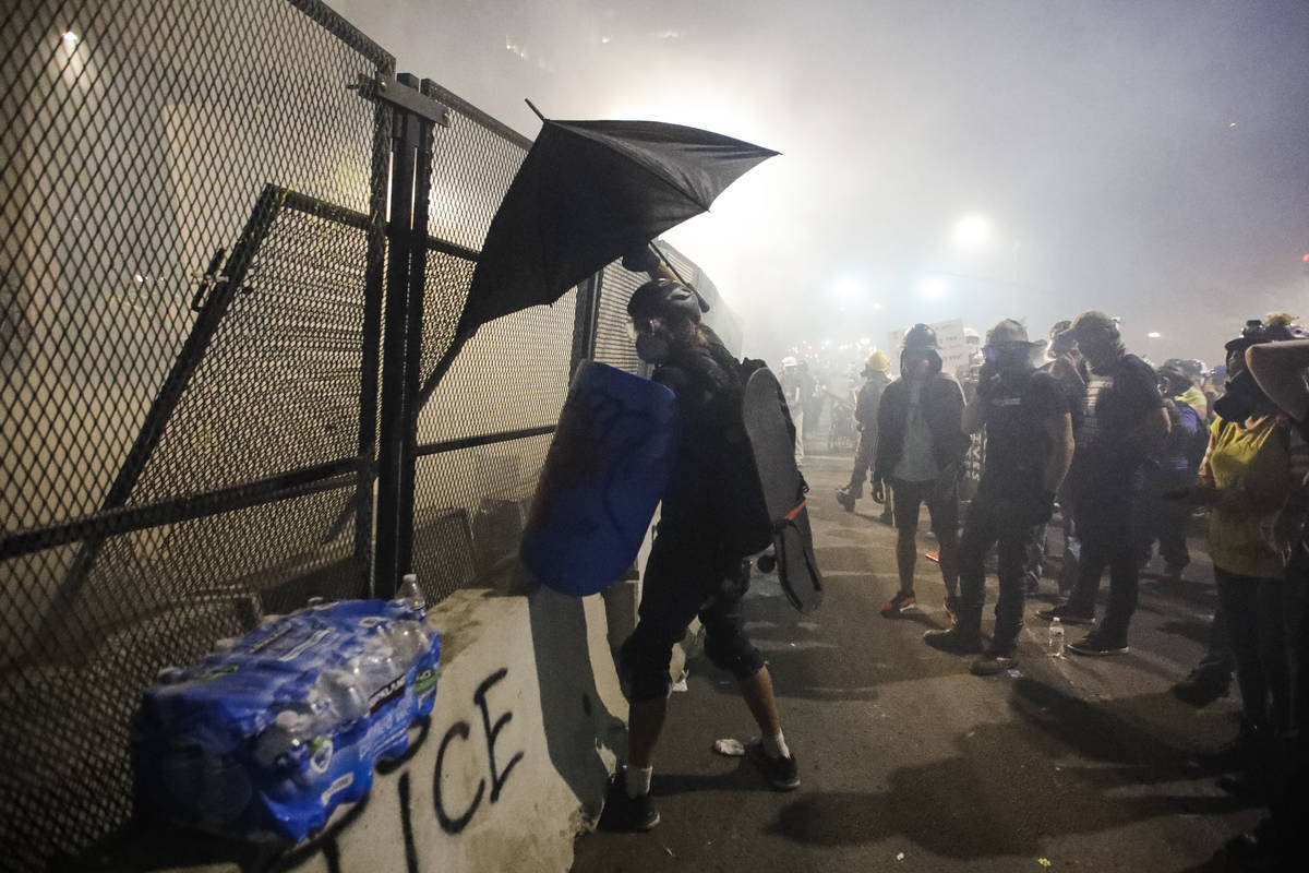 Demonstrators are tear-gassed by federal officers during a Black Lives Matter protest at the Ma ...