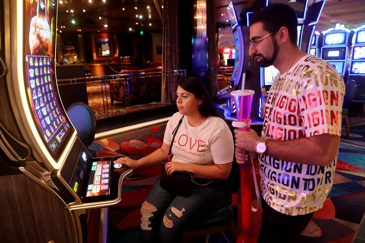 Arash Shahbazian and Michelle Muniz of Los Angeles play a slot machine at the Bellagio on the L ...