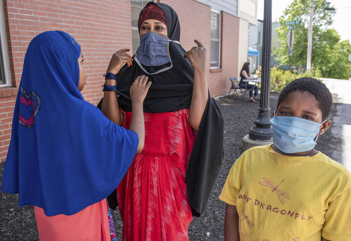 FILE - In this July 25, 2020, file photo, Asha Dere, center, gets some help putting on her new ...