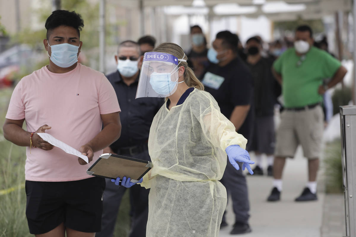 In this July 22, 2020, file photo, people line up behind a health care worker at a mobile Coron ...