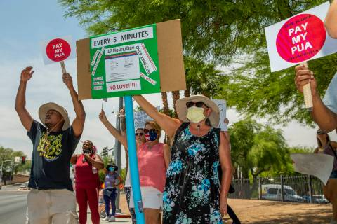 Gig workers gather with signs and wave to passing motorists to protest the Nevada unemployment ...