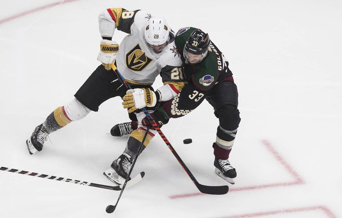 Arizona Coyotes' Alex Goligoski (33) and Vegas Golden Knights' William Carrier (28) battle for ...