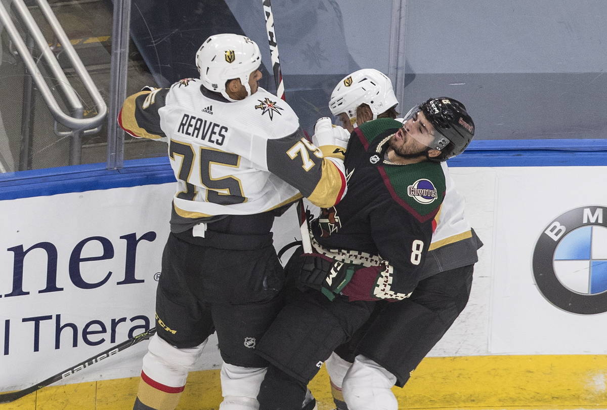 Arizona Coyotes' Nick Schmaltz (8) is checked by Vegas Golden Knights' Ryan Reaves (75) and Zac ...