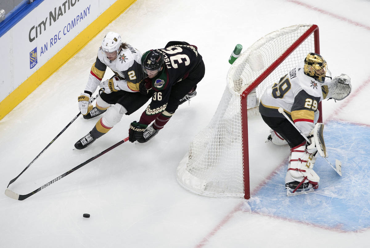 Arizona Coyotes' Christian Fischer (36) and Zach Whitecloud (2) battle for the puck as Vegas Go ...