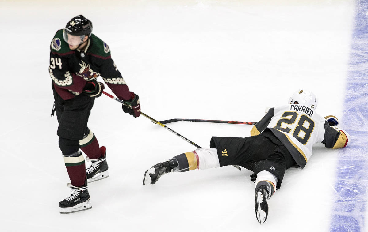 Arizona Coyotes' Carl Soderberg (34) drags Vegas Golden Knights' William Carrier (28) across th ...
