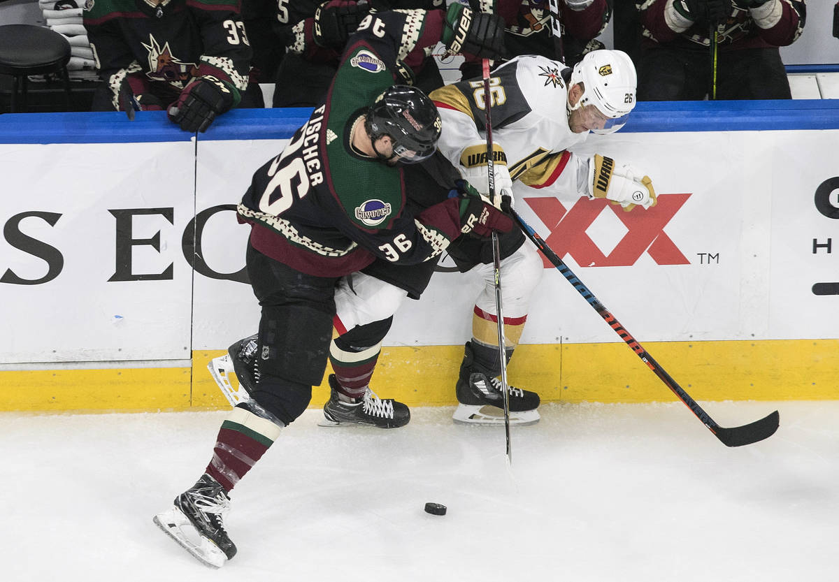 Arizona Coyotes' Christian Fischer (36) checks Vegas Golden Knights' Paul Stastny (26) during t ...