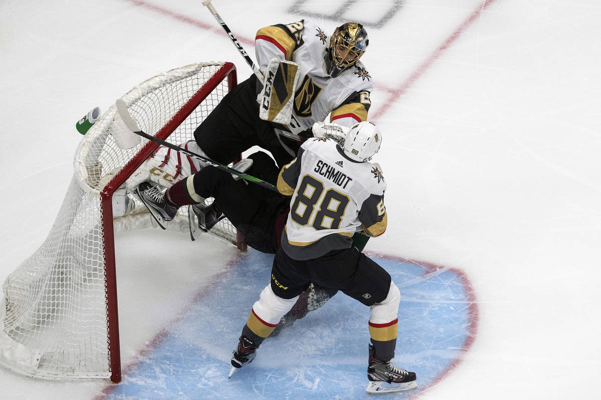 Arizona Coyotes' Taylor Hall (91) crashes into Vegas Golden Knights goalie Marc-Andre Fleury (2 ...
