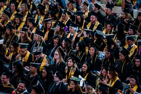 In this 2018, file photo, graduates sit and talk among each other at the start of Nevada State ...