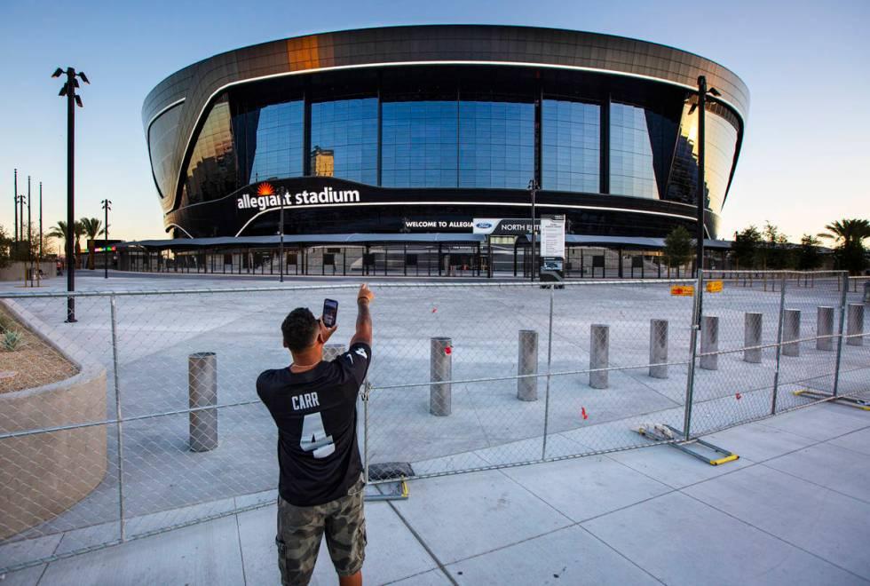Las Vegas Raiders fan Paul Davis, of Santa Maria, Calif., points to Allegiant Stadium while rec ...