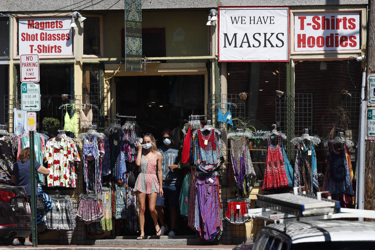 Shoppers leave a clothing shop that now also sells masks to help fight the spread of the corona ...