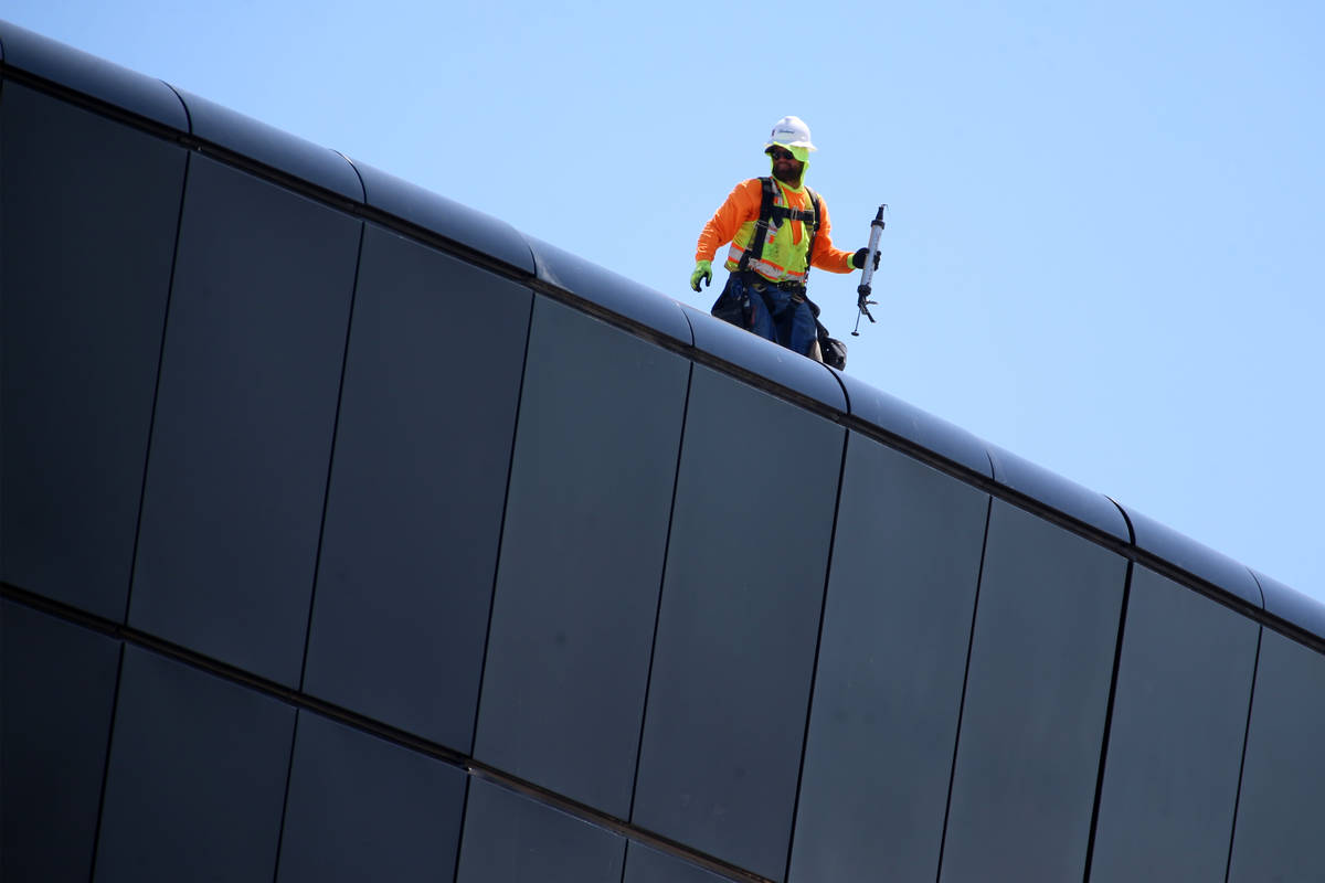 A worker stands of the roof of the Raiders Allegiant Stadium in Las Vegas, Tuesday, April 21, 2 ...