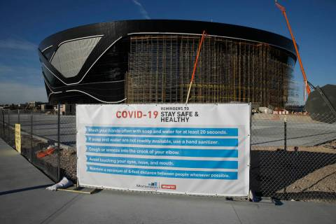 A sign gives guidelines for protection from COVID-19 as construction continues at Allegiant Sta ...