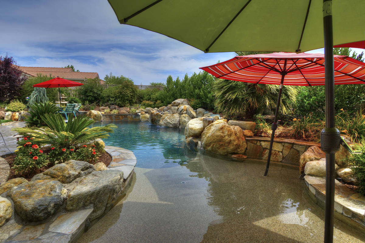 This freeform pool has colorful umbrellas, rock features and a pebble interior. (Premier Pools ...