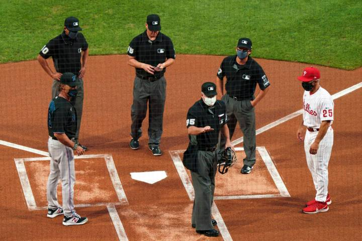 FILE - In this Friday, July 24, 2020, file photo, home plate umpire Tim Timmons, center, explai ...