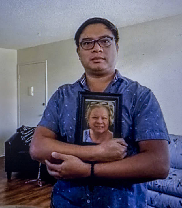 Roderick Alimusa holds a photograph of his mother, Maria Alimusa, who died at The Heights of Su ...