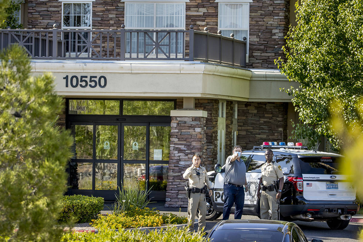 The manager of The Heights of Summerlin gestures beside two Las Vegas Police officers outside, ...