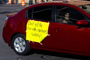 People participate in a car caravan on the Las Vegas Strip led by the Culinary Union on Tuesday ...