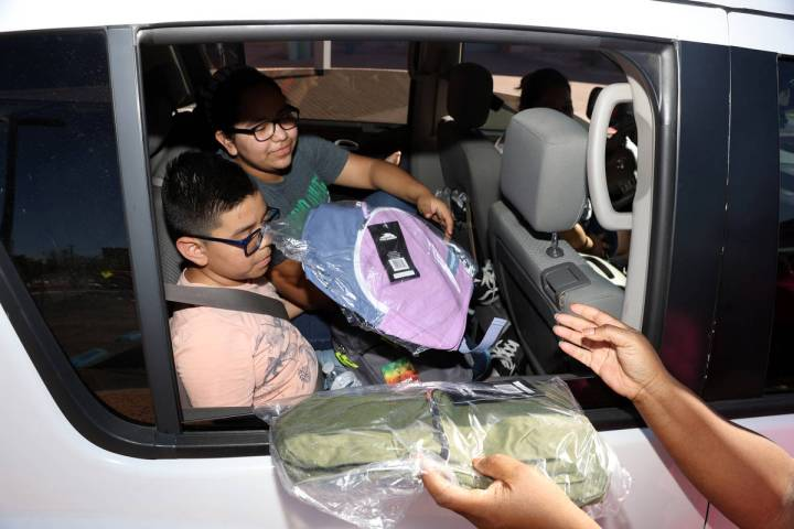 Ashelyn Reyes, 12, and her brother Pablo, 10, receive free backpacks during an event hosted by ...