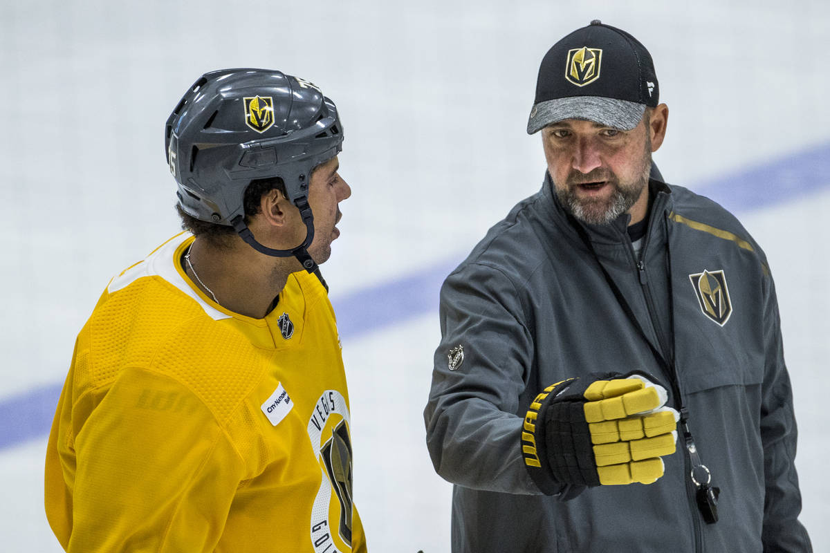 Vegas Golden Knights right wing Ryan Reaves (75, left) listens on the ice to head coach Peter D ...
