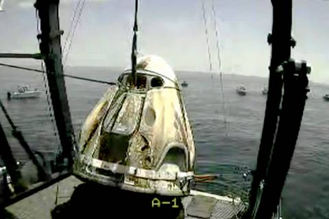 In this frame grab from NASA TV, the SpaceX capsule is lifted onto a ship, Sunday, Aug. 2, 2020 ...