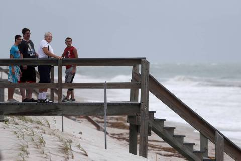 Beach goers watch waves churned up by Tropical Storm Isaias near Jaycee Beach Park, Sunday, Aug ...
