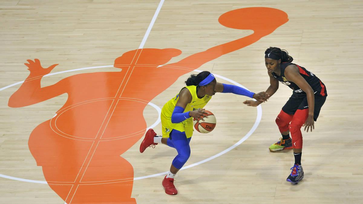 Dallas Wings' Arike Ogunbowale, left, moves the ball through midcourt as Las Vegas Aces' Sugar ...