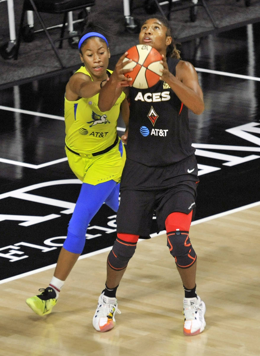 Dallas Wings' Tyasha Harris, left, defends against Las Vegas Aces' Angel McCoughtry during the ...