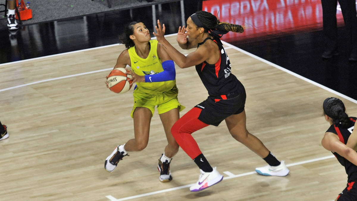 Dallas Wings' Satou Sabally, left, looks to shoot as Las Vegas Aces' A'ja Wilson defends during ...